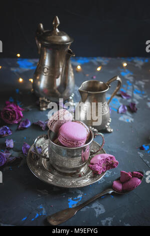 Freshly baked macaroons on a silver metal Cup with bokeh from the lights on the wooden background. Selective focus. Copy spase - Stock Photo