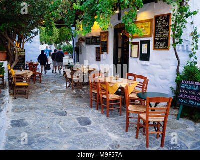 Amorgos ,Greece-August 1,2017.A small traditional tavern next to its central pedestrian street of Chora ,Amorgos at sunset. - Stock Photo