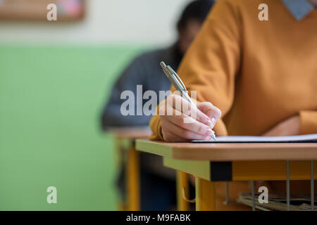 Students taking exam in classroom. Education test and literacy concept. Cropped shot, hand detail. - Stock Photo
