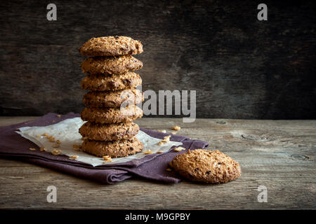 Homemade wholegrain cookies with oatmeal, lin and sesame seeds on dark rustic wooden table, copy space. Healthy vegan wholegrain cookies. - Stock Photo