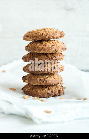 Homemade wholegrain cookies with oatmeal, lin and sesame seeds on white wooden table, copy space. Healthy vegan wholegrain cookies. - Stock Photo