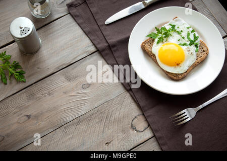 Fried Egg on Wholegrain Toast and cup of Coffee for Breakfast. Fried egg with bread on plate over wooden table, top view, copy space. - Stock Photo