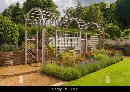 Summer view of sunlit tunnel arbour & colourful herbaceous borders - beautiful, designed, landscaped, traditional garden, West Yorkshire, England, UK. - Stock Photo