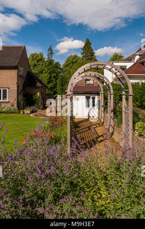 Summer view of sunlit tunnel arbour & colourful herbaceous border - beautiful, designed, landscaped, traditional garden, West Yorkshire, England, UK. - Stock Photo