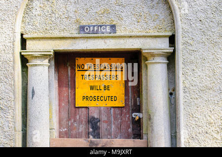 Sign at a building warning that trespassers will be prosecuted. - Stock Photo