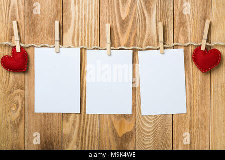 Blank sheet of paper hand made heart pinned to rope on wooden background - Stock Photo