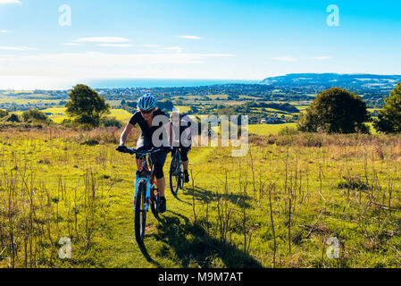 Two female cyclists climb onto Brading Down between Sandown and Ryde in the Isle of Wight, one on a mountain bike, one on a gravel bike - Stock Photo