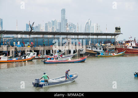 Panama City, Panama - march 2018: Fishermen and boats on fish market / harbour with city skyline, Panama City. - Stock Photo