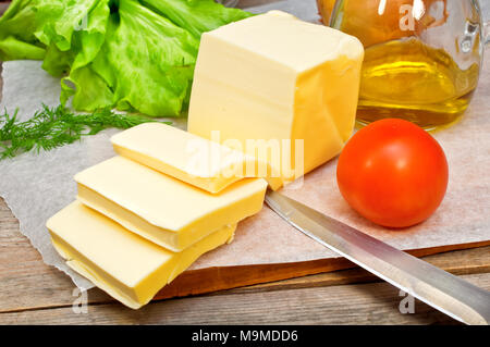 butter in parchment paper and vegetables on a wooden table  - Stock Photo