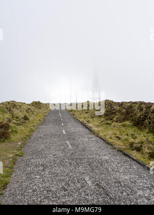 High Road to the Clouds: A small paved road curves toward some fog enshrouded communication towers high on the hills above Lagoa do Fogo. - Stock Photo