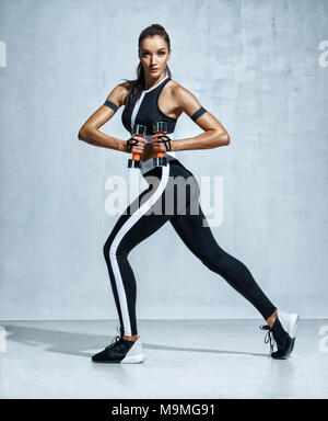 Young latin woman doing exercise with dumbbells. Photo of sporty woman in training pumping up muscles hands on grey background. Strength and motivatio - Stock Photo