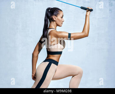 Strong woman using resistance band in her exercise routine. Photo of fitness model workout on grey background. Strength and motivation - Stock Photo