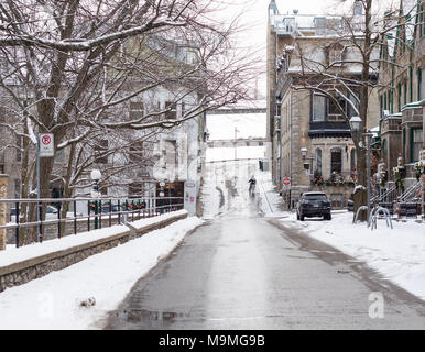 Woman with Bicycle on Old Quebec street in winter: A woman walks her bicycle down a snowy, steep street in Old Quebec near the citadel. - Stock Photo