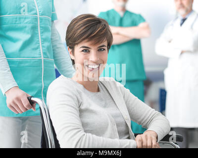 Smiling young disabled patient at the hospital, a nurse is pushing her wheelchair, medical staff and doctors working on the background - Stock Photo