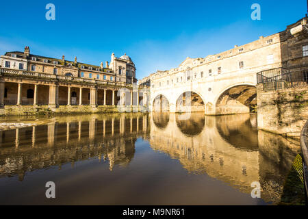 Historic Pulteney Bridge's three arches and the Grand Parade columns reflected in the  shimmering River Avon in Bath with a beautiful clear blue sky - Stock Photo