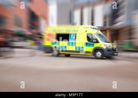 NHS ambulance with blue lifghts in city UK - Stock Photo