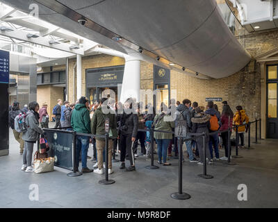 KINGS CROSS STATION:  People queuing for the Harry Potter Shop at Platform 9 3/4 - Stock Photo