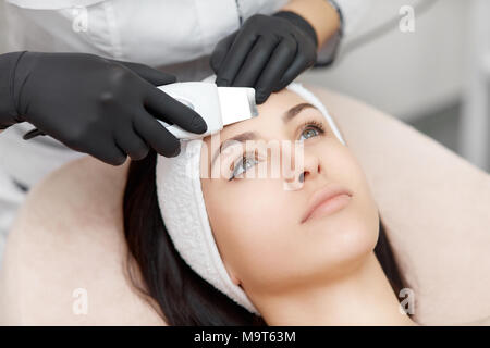 Hands of beautician doing facial in beauty salon. - Stock Photo