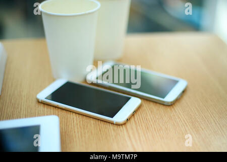 Two white mobile phones with tablet on wooden table background, blank screen electronic device with copy space. - Stock Photo