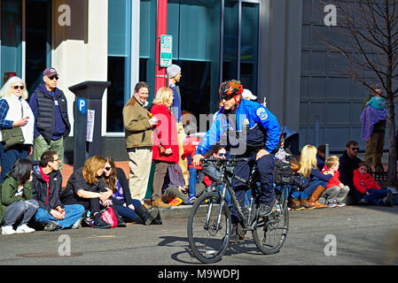 Police on bicycle controlling crowd at event - Stock Photo