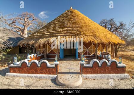 Traditional hut accommodation at Planet Baobab in Botswana, Africa. - Stock Photo