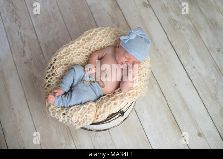 Six week old baby boy wearing light blue pjs and lying in a round, bucket. Shot in the studio on a light wood background. - Stock Photo
