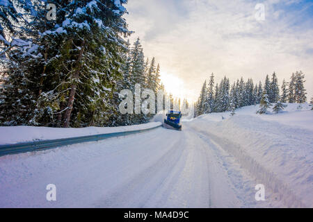 Reinli, Norway - March 26, 2018: Outdoor view of snow-removing machine cleans the street of the road from the snow in the morning snow-covered trees a - Stock Photo