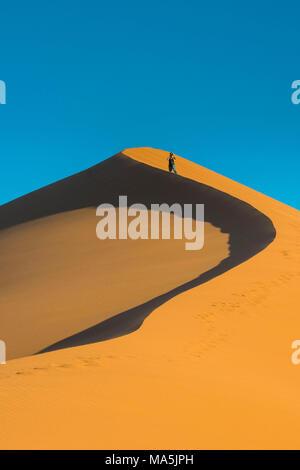 Woman hiking up the  giant sand Dune 45, Namib-Naukluft National Park, Namibia - Stock Photo
