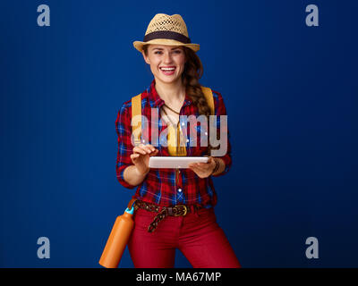Searching for inspiring places. happy active tourist woman with backpack using tablet PC isolated on blue background - Stock Photo