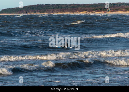 winter surfer in baltic sea small waves - Stock Photo