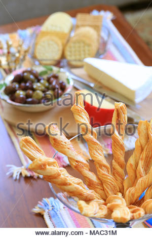Cocktail hor d'oeuvres on a coffee table, including grissini (Italian breadsticks), mixed olives, gouda, brie and an assortment of water crackers. - Stock Photo