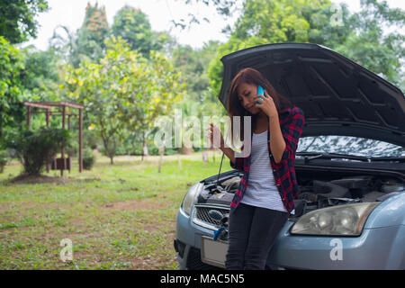 Young woman with car breaks down and she is calling the emergency services. - Stock Photo