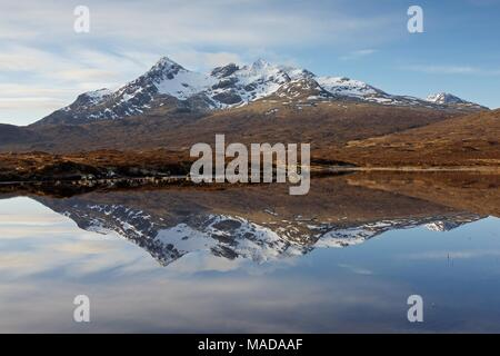 A colour image taken on a springs morning of the mirror reflection of the peak of Sgurr Nan Gillean in the still waters of Loch Caol at Sligachan - Stock Photo