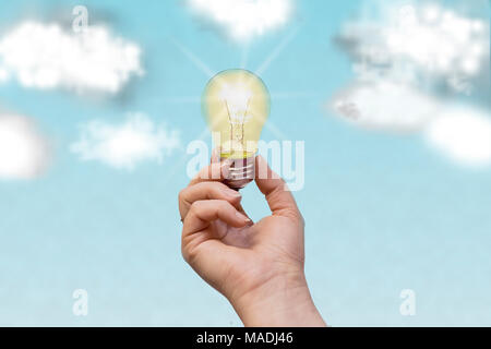 The man's hand holds a glowing lamp against the blue sky. Symbol of wireless energy, progress, success. - Stock Photo