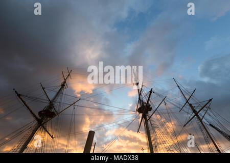 Vibrant orange clouds in a dramatic sky above the wooden masts of HMS Gannet at The Historic Dockyard, Chatham, Kent, UK just before sunset. - Stock Photo