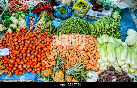 Abundance of herbs and vegetables displayed at a local Indonesian market in North Sumatra - Stock Photo