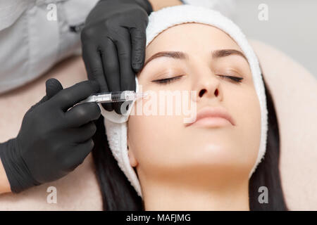 Close-up of beautiful woman with closed eyes getting injection in her face, making her skin lifted and smooth. Hands of professional cosmetologist hol - Stock Photo