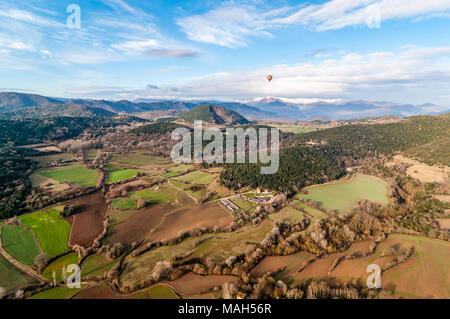 Hot air balloon flying with croscat open volcano and mountains on the background, cloudy day, Olot, Catalonia, Spain - Stock Photo