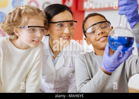Schoolboy showing flask with substance proudly to teacher and classmate - Stock Photo
