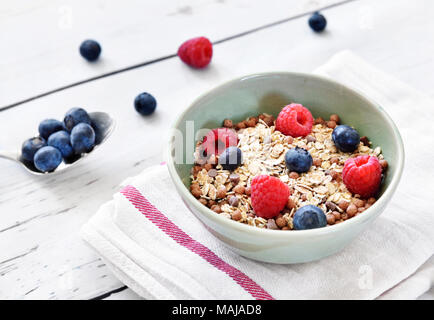 Cereals in a bowl, breakfast scene with fresh fruits and muesli, healthy eating. Breakfast bowl on a wooden table, rustic scene. - Stock Photo