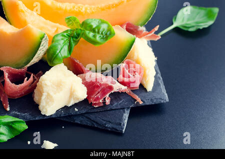 Concept of italian food with melon and prosciutto on dark background. Traditional appetizer antipasto. Selective focus. - Stock Photo