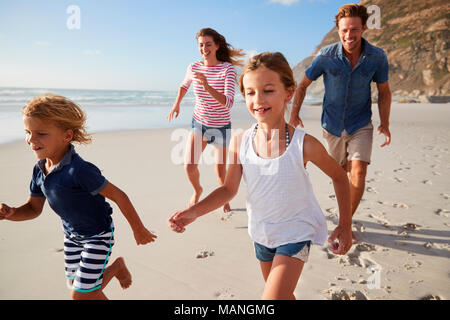 Parents Running Along Beach With Children On Summer Vacation - Stock Photo