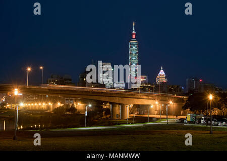 The bright lights of the Taipei skyline at night against a dark evening sky seen from the Taipei River Park along the Keelung River. Minquan Bridge in - Stock Photo