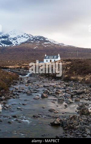 Allt Dearg holiday cottage near Sligachan with Sgurr Nan Gillean, Cuillin mountain, Isle of Skye, Scotland, UK in March - long exposure - Stock Photo