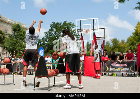 A young man takes part in the three-point shot contest, which was part of a 3-on-3 basketball tournament in downtown Athens, GA on August 24, 2013. - Stock Photo