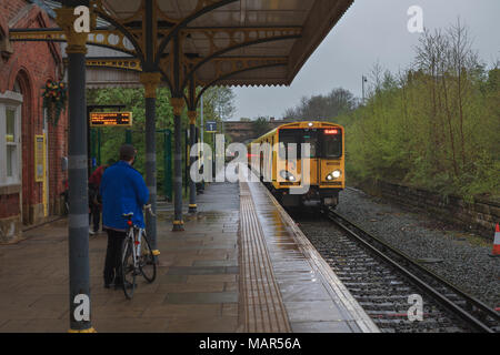 A Merseyrail train arriving at  Ormskirk railway station from Liverpool with a cyclist waiting to board the train with his bike - Stock Photo