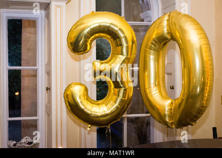 Golden number 30 thirty made of inflatable balloons, private party at home. - Stock Photo