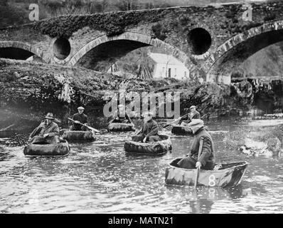 Group of men fishing for salmon in coracles on the River Teifi at Cenarth, on the border of Pembrokeshire, Ceredigion, and Carmarthenshire in Wales. Black and white photograph. The Cenarth Bridge, or Pont Canarth in Welsh, in the background. Mid 20th century. - Stock Photo