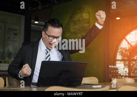 Work complete. Businessman specialist rejoicing her finished work with raised fists sitting at her desk. - Stock Photo