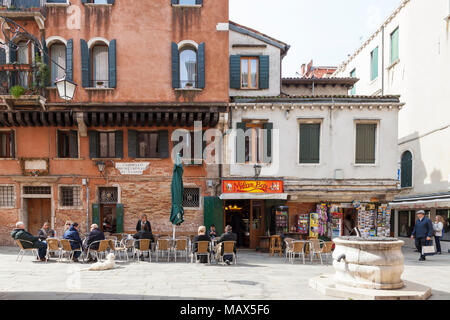 Local Venetians and tourists drinking outside the popular Milan Bar, Cannaregio, Venice, Italy  with a pozzo or ancient well in the foreground - Stock Photo